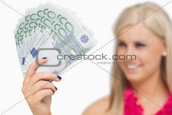 Blonde showing 100 euros banknotes