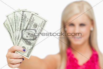 Beautiful blonde holding 100 dollars banknotes