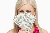 Blonde hiding her face with 100 dollars banknotes