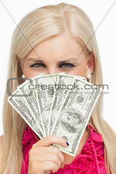 Blonde hiding her face with dollars banknotes