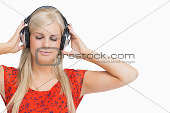 Blonde in orange dress listening to music