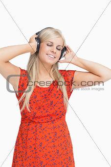 Smiling blonde in orange dress listening to music