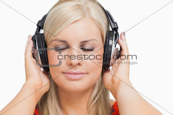 Blonde in dress listening to music