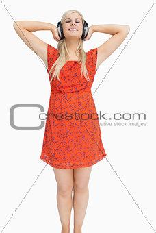 Blonde listening to music in orange dress