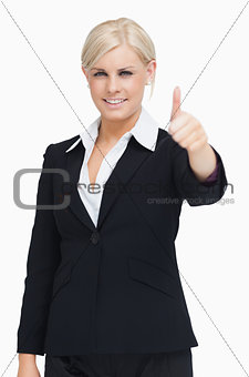 Smiling blond businesswoman thumb-up