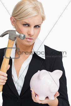Beautiful businesswoman holding a hammer and a piggy-bank