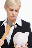Sad businesswoman holding a hammer and a piggy-bank