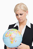 Stern businesswoman holding a globe