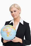 Serious businesswoman holding a globe