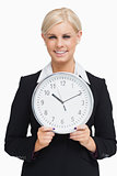 Serious blonde in suit holding a clock