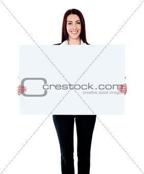 Caucasian businesswoman holding a blank billboard
