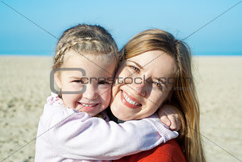 Autumn at the sea: happy mother and adorable little girl