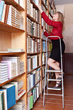 student is looking books on the shelves standing on a ladder