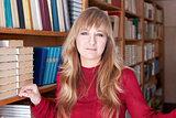 woman stands near the bookshelves