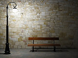 Illuminated brick wall with old fashioned street light and bench