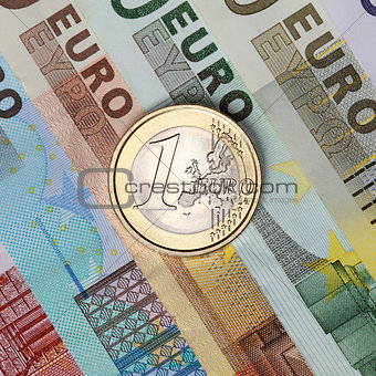 One Euro coin on banknotes