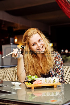 A young woman having lunch at a cafe laughing