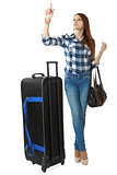 A young girl with a big, black travel bag on wheels, looks timet