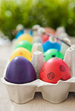 Colorful painted Easter eggs in a carton on the green background