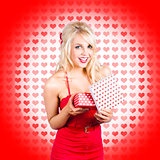 Stunning young blond beauty holding heart present