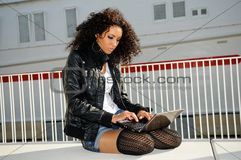 Portrait of black girl with laptor computer in urban background