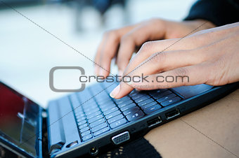 Hands of a businesswoman writting with a laptop computer