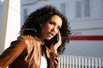Portrait of pretty black woman in urban background talking on phone