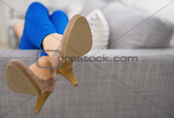 Closeup on legs laying on couch woman