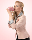 girl kissing her piggybank