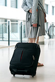 Woman's legs and travel suitcase at international airport