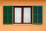 opened green window shutters on yellow house facade