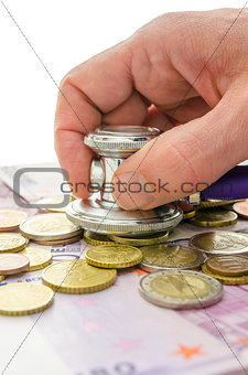 Detail of male hand checking money with stethoscope