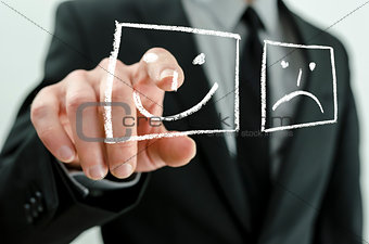 Business man choosing smiling icon on a virtual board