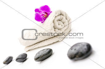 Massage stones and violet orchid flower on a towel