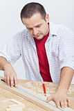 Woodwork - man measuring wooden planck
