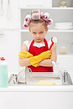 Grumpy little girl washing dishes