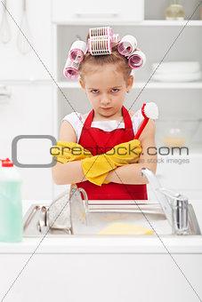 Grumpy little girl washing dishes