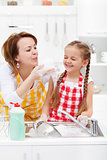 Woman and little girl having fun washing the dishes