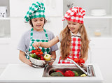 Kids washing vegetables in the kitchen