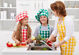 Woman and kids washing vegetables in the kitchen