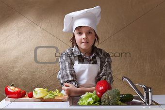 Little boy with chef hat washing vegetables