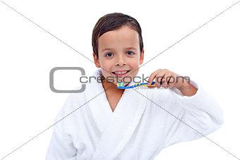 Little boy in bathrobe washing teeth