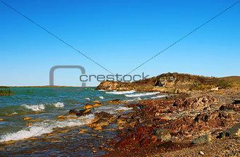 Stony coast leaving for horizon with blue sea water
