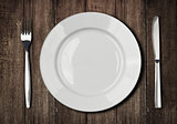 white plate, knife and fork on old wooden table