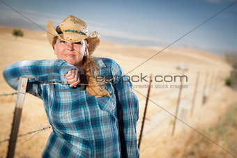 Beautiful Cowgirl Against Wire Fence in Field