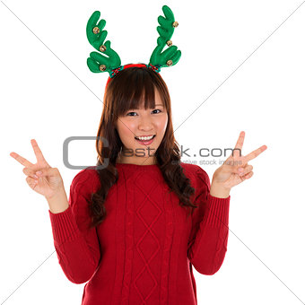 Asian Christmas girl showing victory sign.