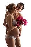 Portrait of young pregnant couple holding flowers
