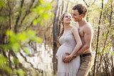Pregnant couple at the river in spring