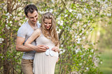 Young pregnant couple outdoors in spring