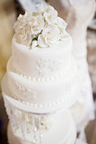 White layered wedding cake with roses on top